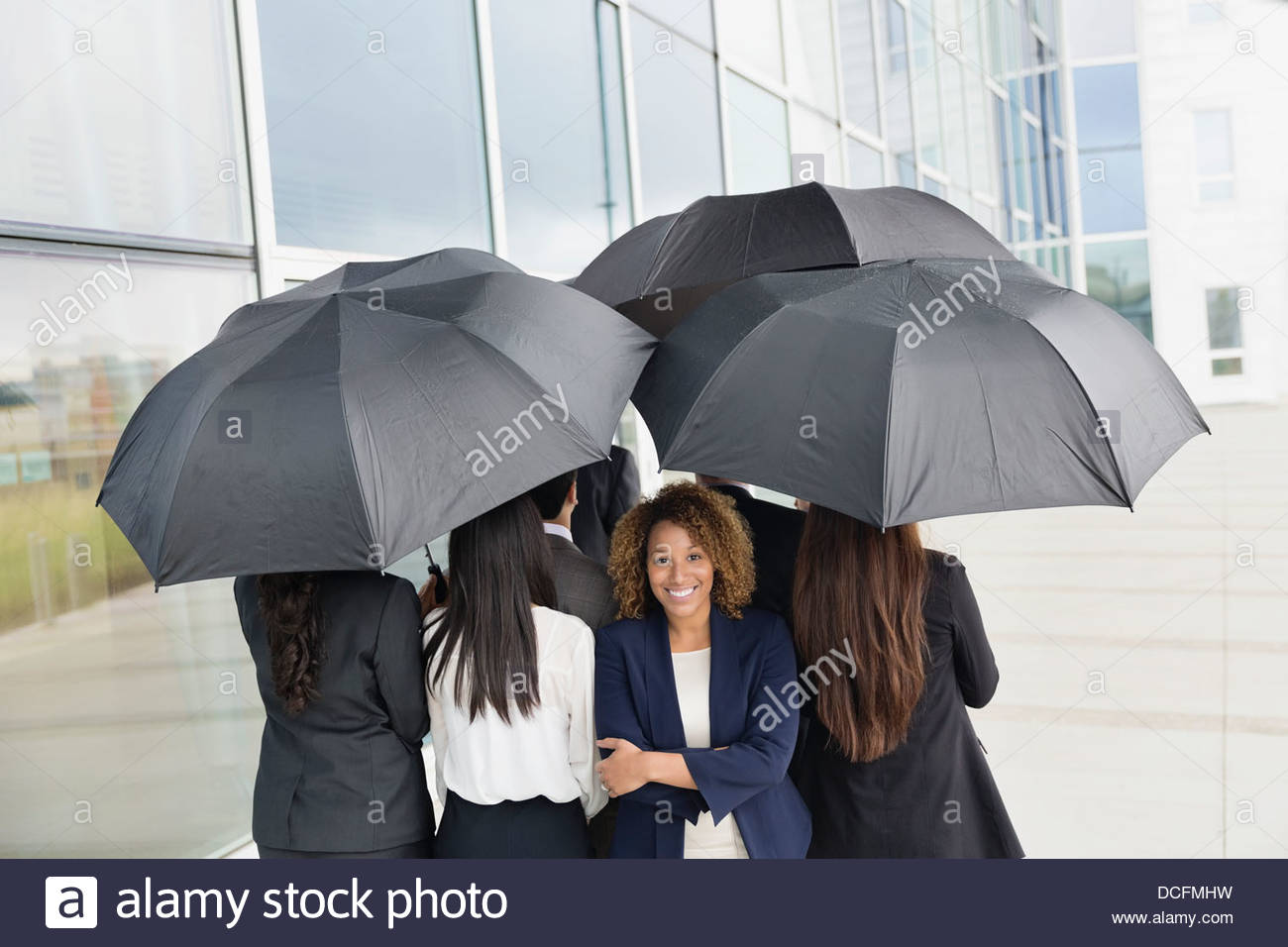 Businesswoman standing out of the crowd - Stock Image