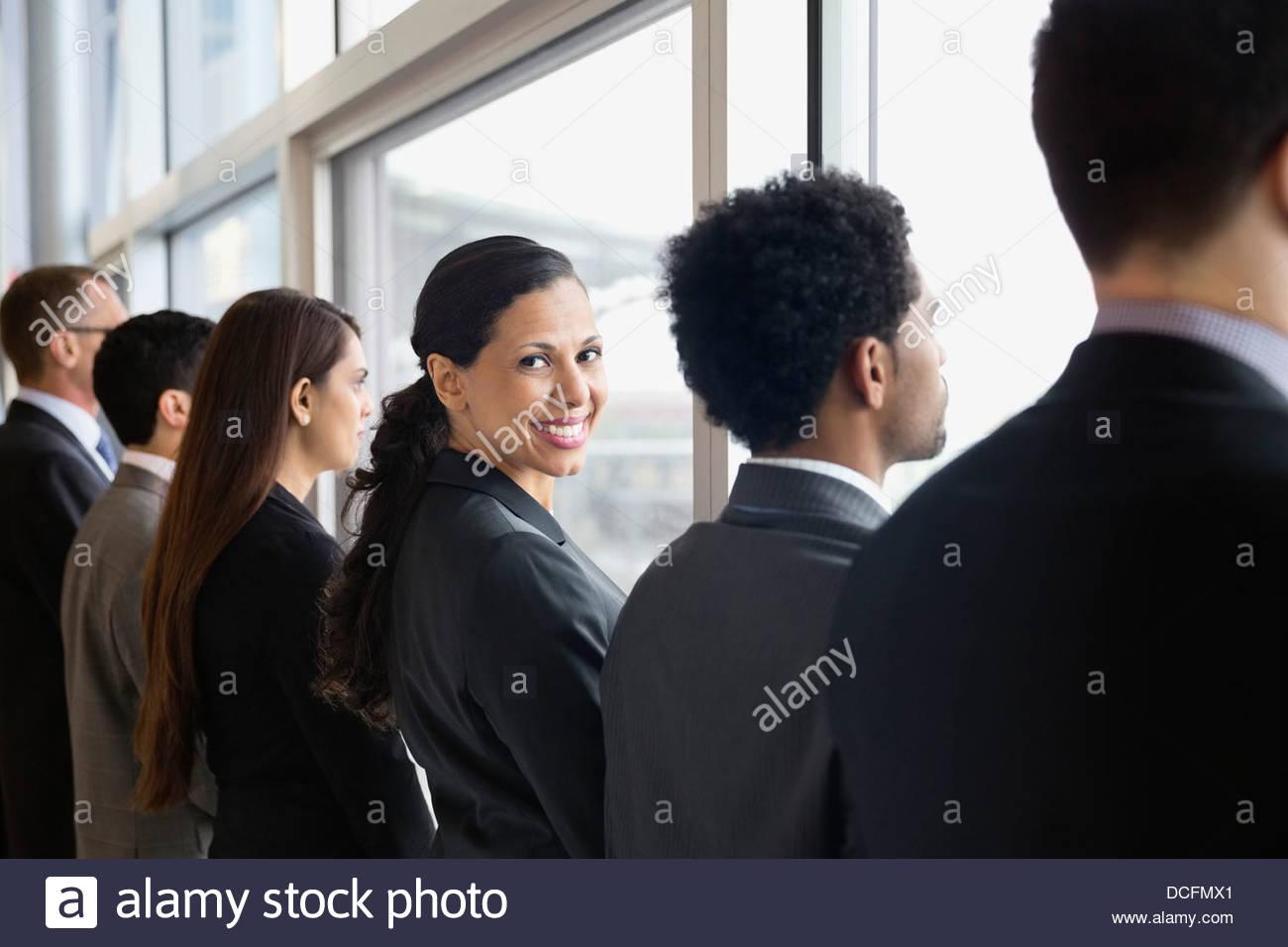 Businesswoman looking over shoulder - Stock Image