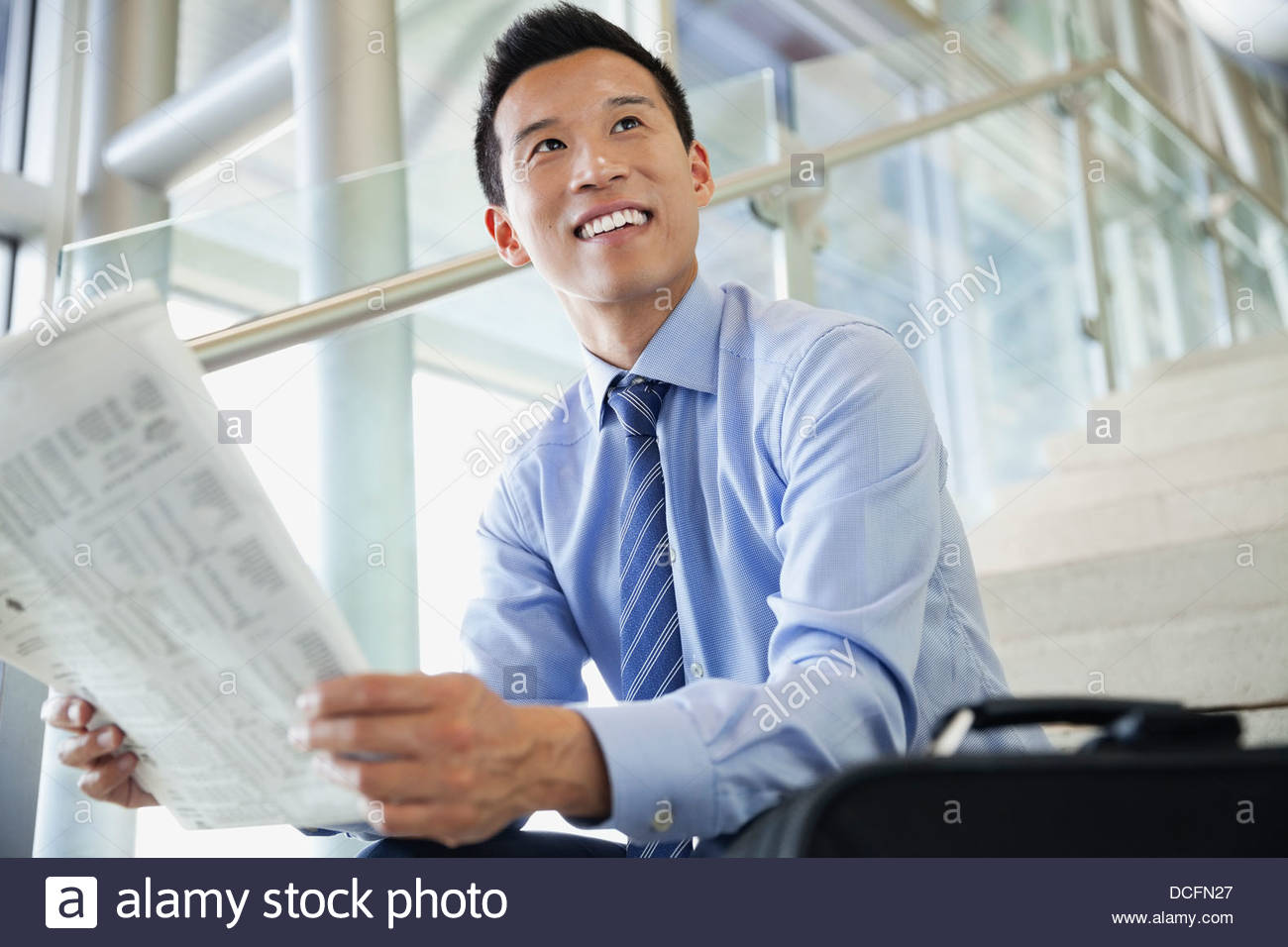 Smiling businessman looking up with newspaper - Stock Image