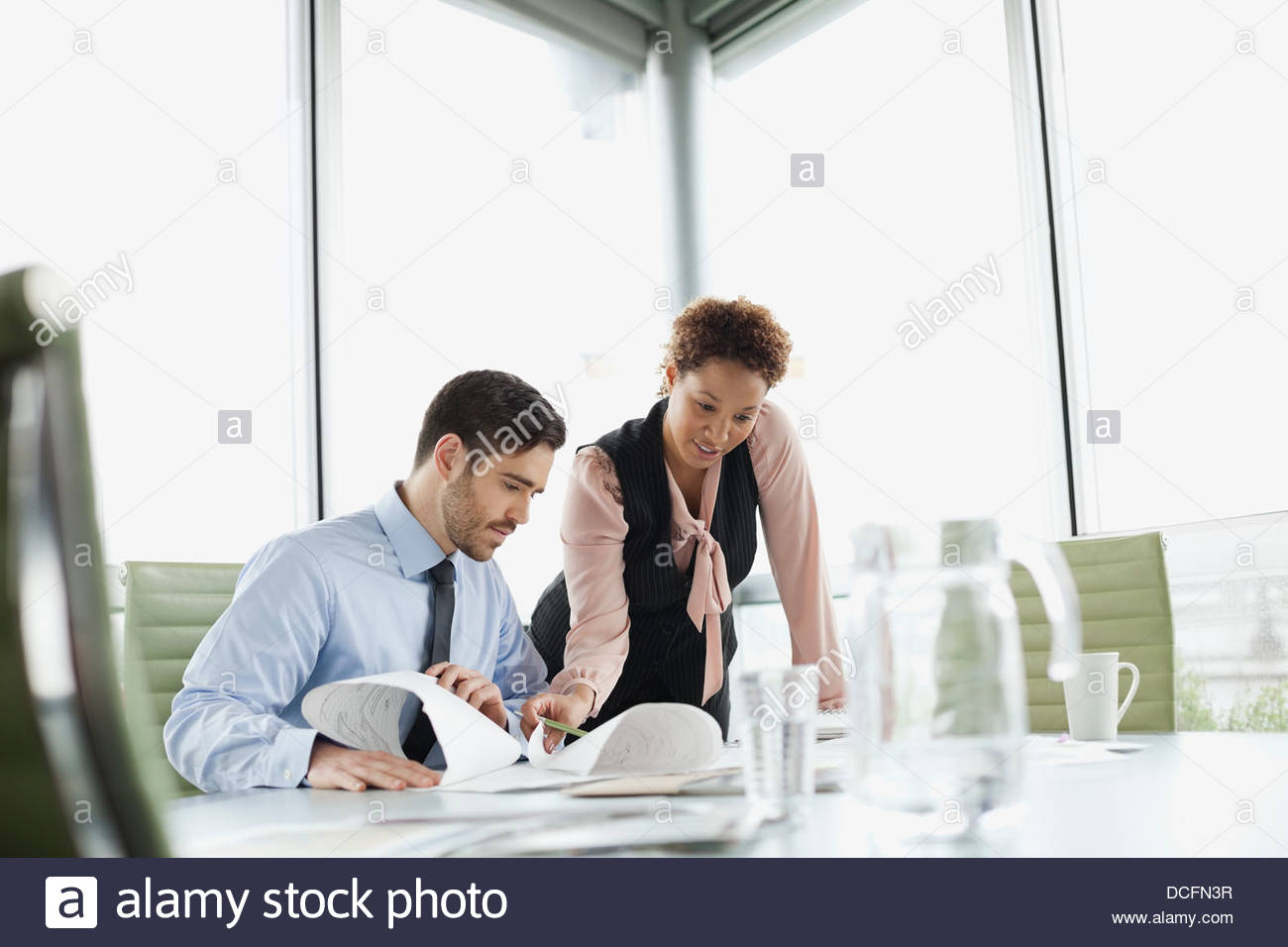 Business colleagues working together in boardroom - Stock Image