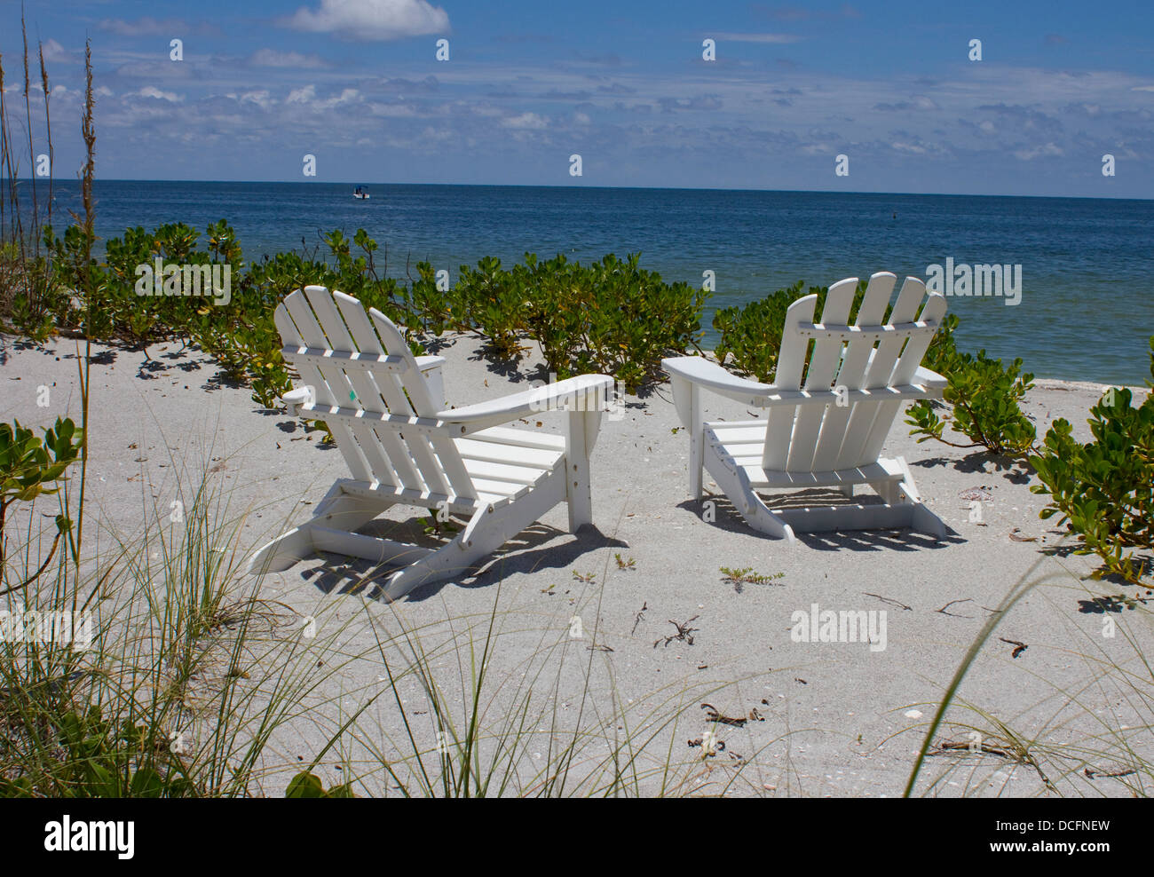 Two Adirondack Chairs On A Beach