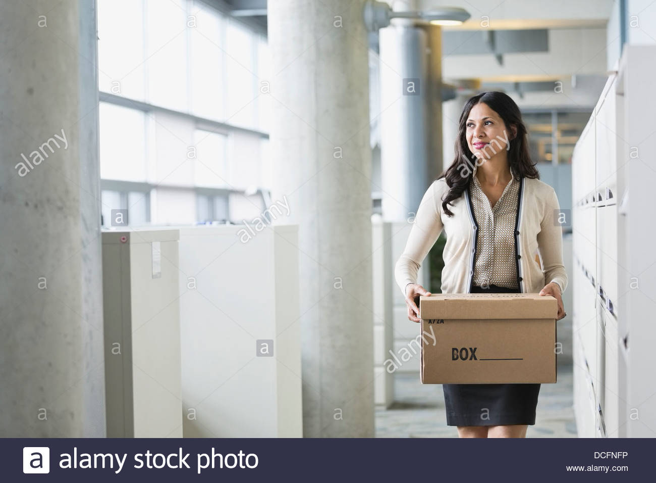 Businesswoman carrying cardboard box - Stock Image