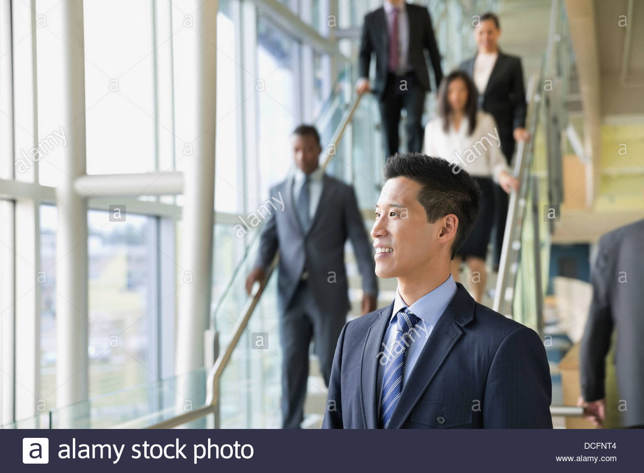 Smiling businessman looking away in office building - Stock Image