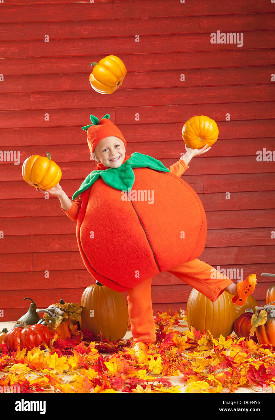 A Child In A Pumpkin Costume Juggling Pumpkins; Three Hills, Alberta, Canada - Stock Image
