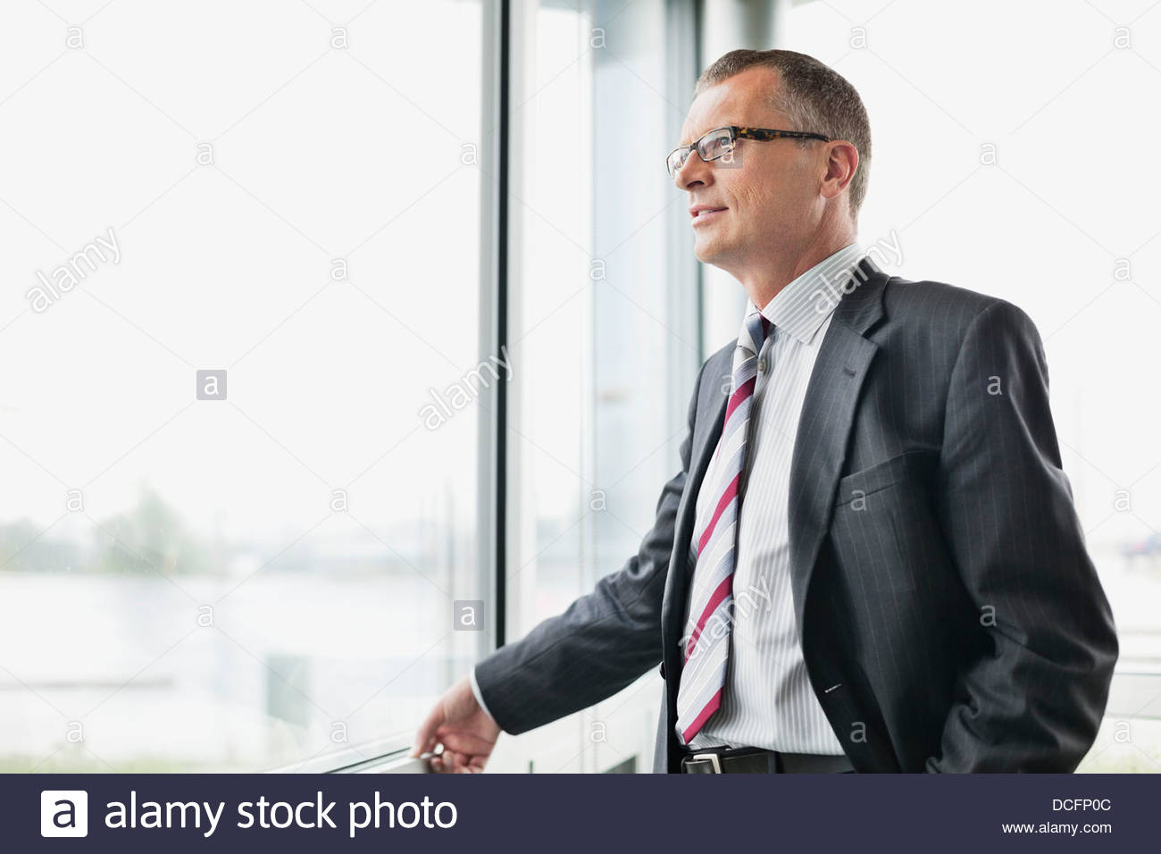 Thoughtful businessman looking out window in office - Stock Image