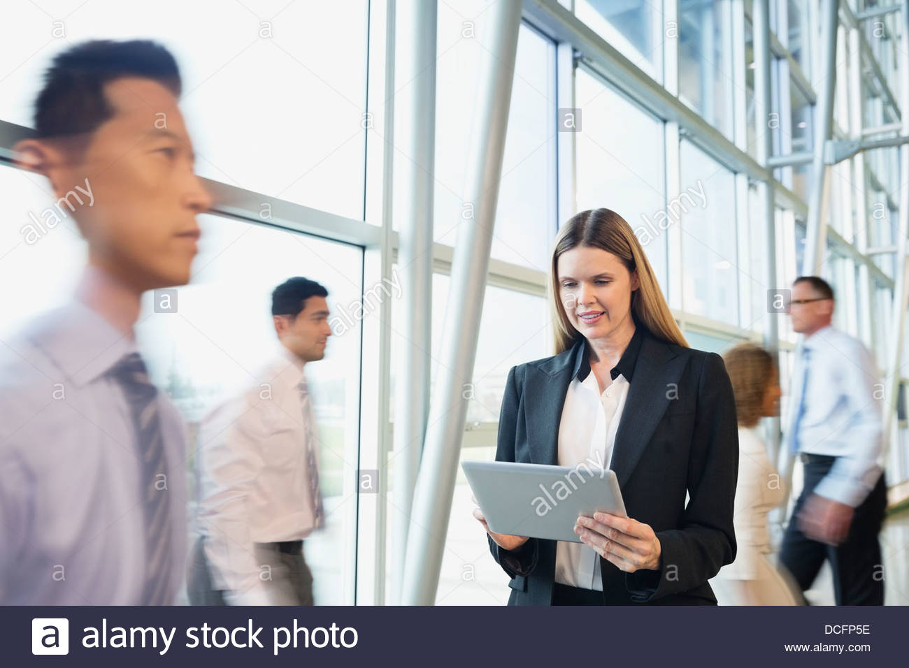 Businesswoman using digital tablet in office building - Stock Image