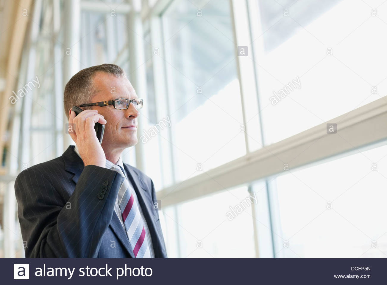 Businessman talking on mobile phone by window - Stock Image