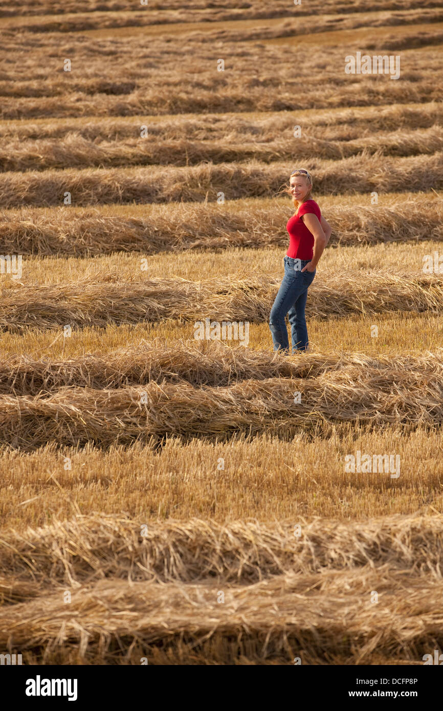A Woman Stands In A Harvested Wheat Field; Three Hills, Alberta, Canada Stock Photo