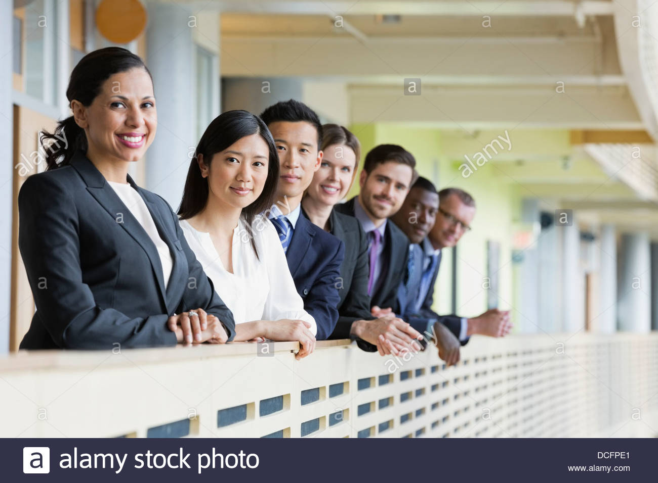 Smiling business colleagues standing in a row - Stock Image