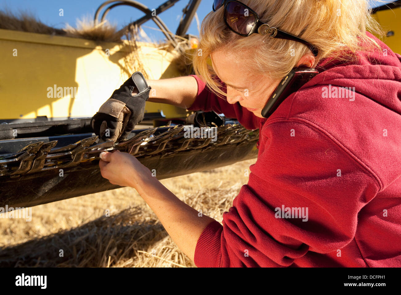 A Woman Works On Her Farm Equipment While Talking On Her Cell Phone; Three Hills, Alberta, Canada - Stock Image
