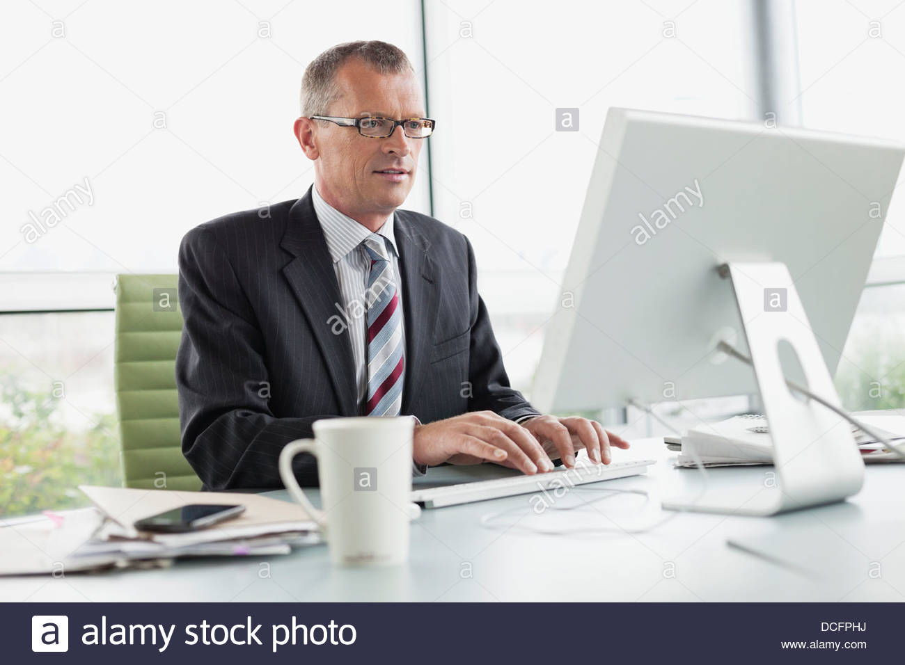 Businessman working on computer in office - Stock Image