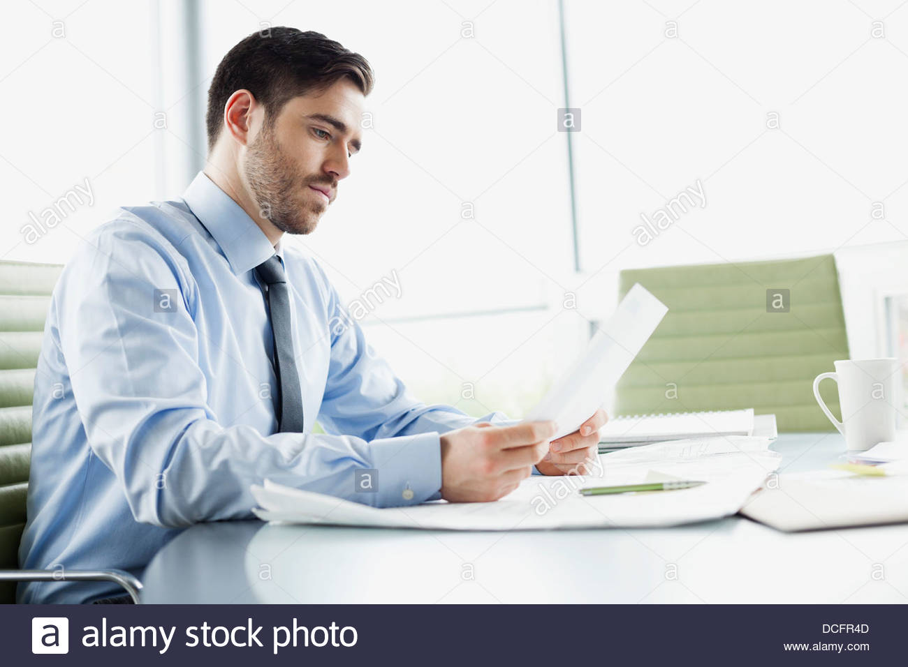Businessman reviewing documents in board room - Stock Image