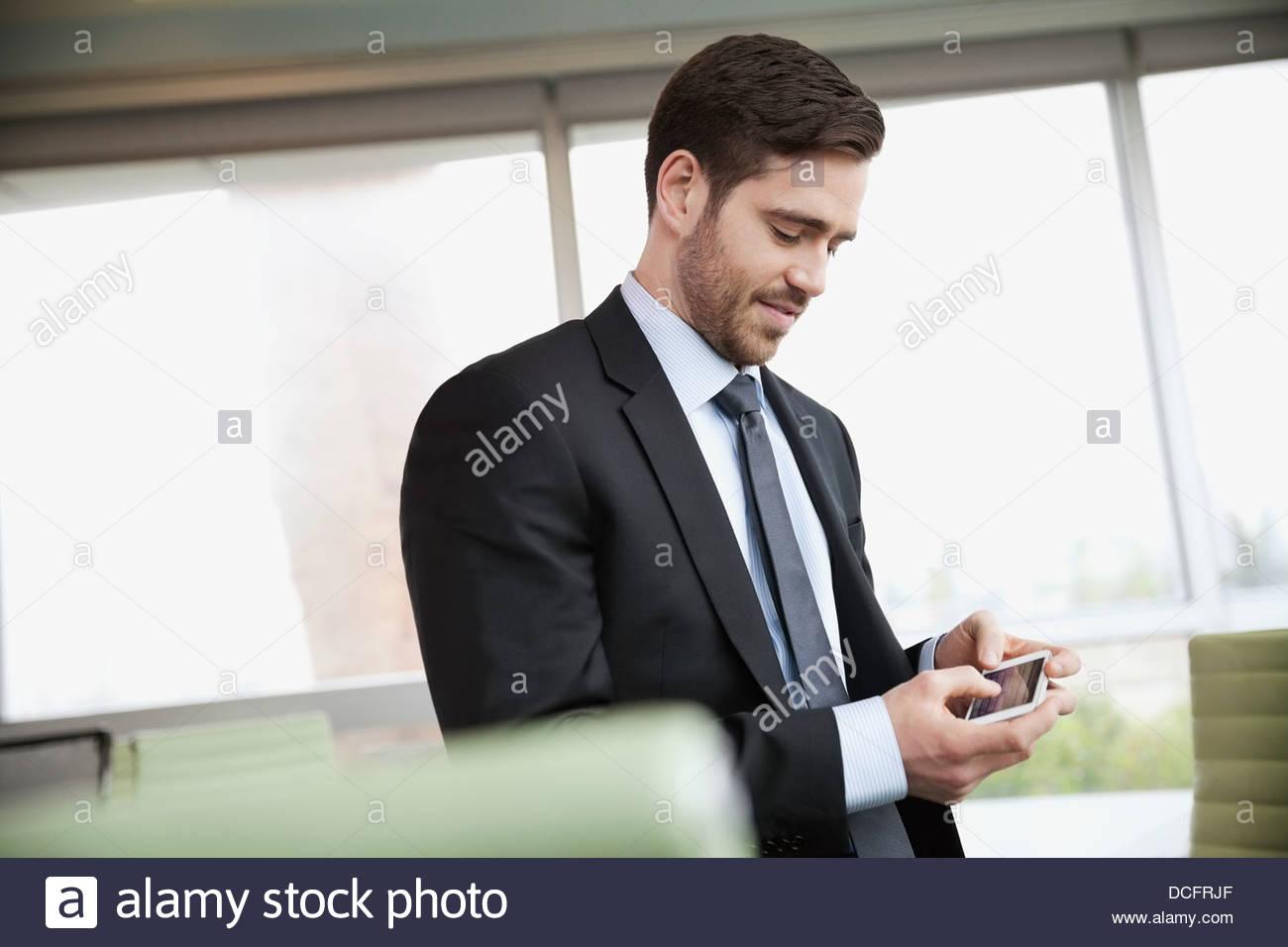 Businessman texting on smart phone - Stock Image