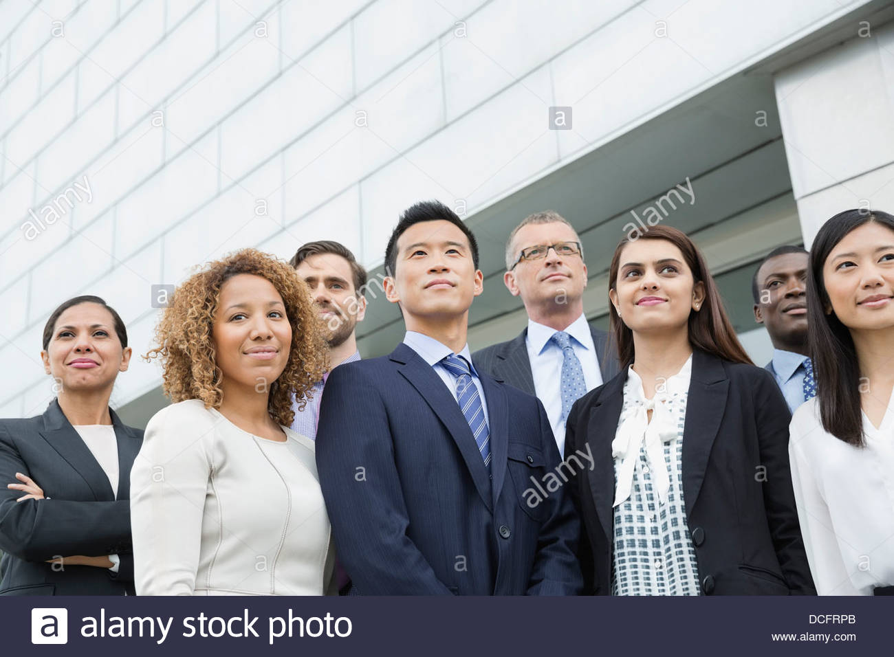 Group of business people standing outdoors - Stock Image