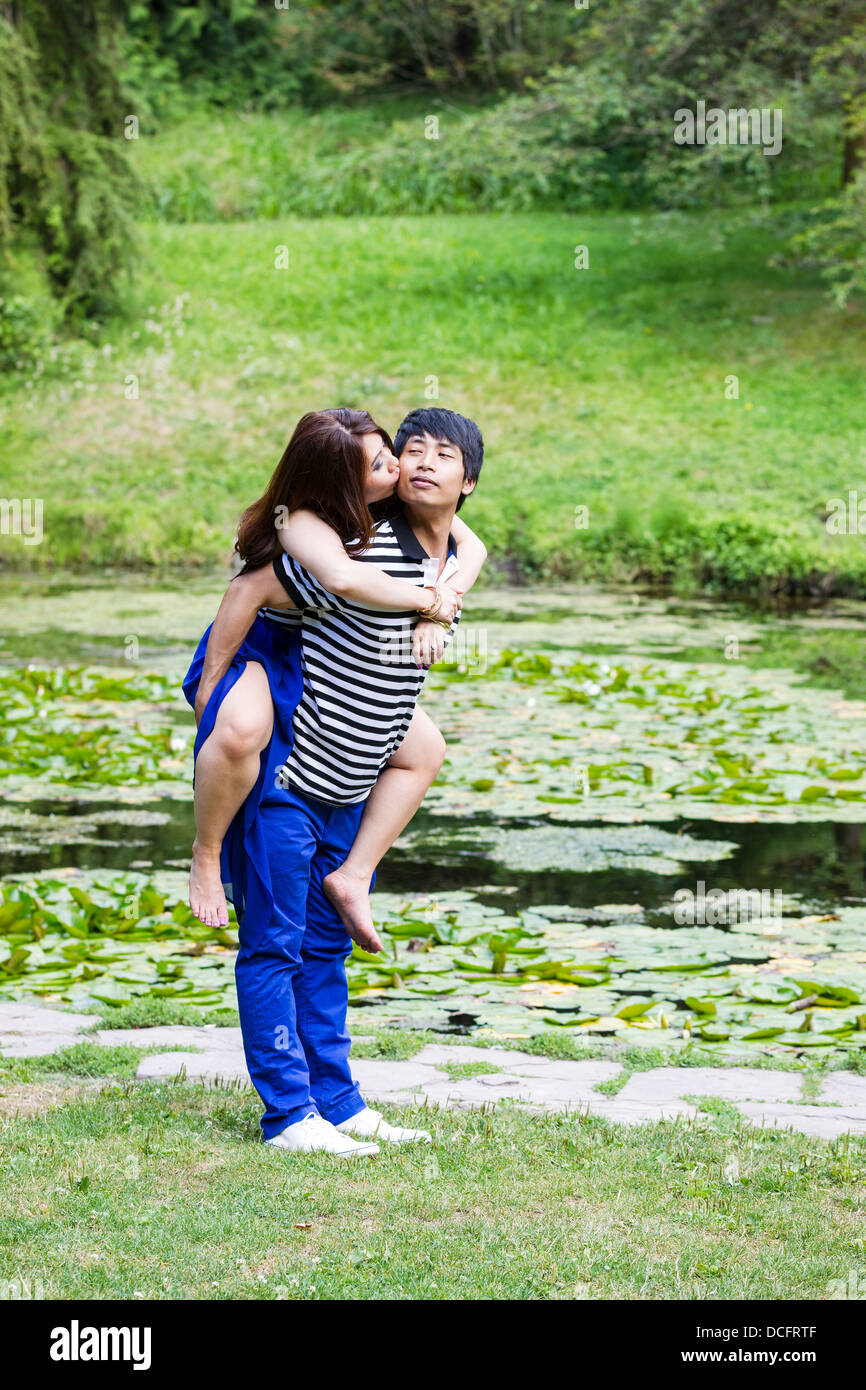 Vertical photo of young adult couple, woman riding on boyfriend back and kissing him, with pond in background - Stock Image