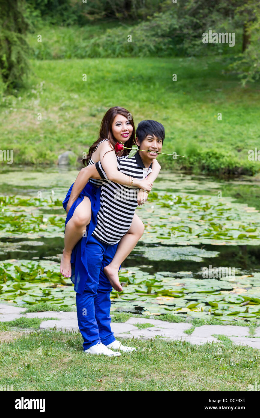 Vertical photo of young adult couple, woman riding on boyfriend back, man holding red rose in mouth with lily pond - Stock Image