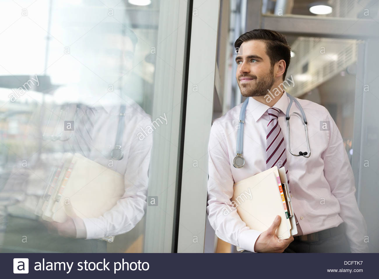 Medical professional leaning against window - Stock Image
