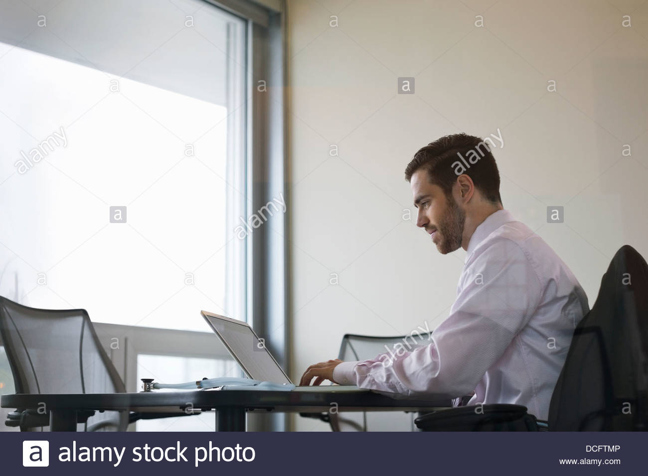 Side view of male doctor using laptop - Stock Image