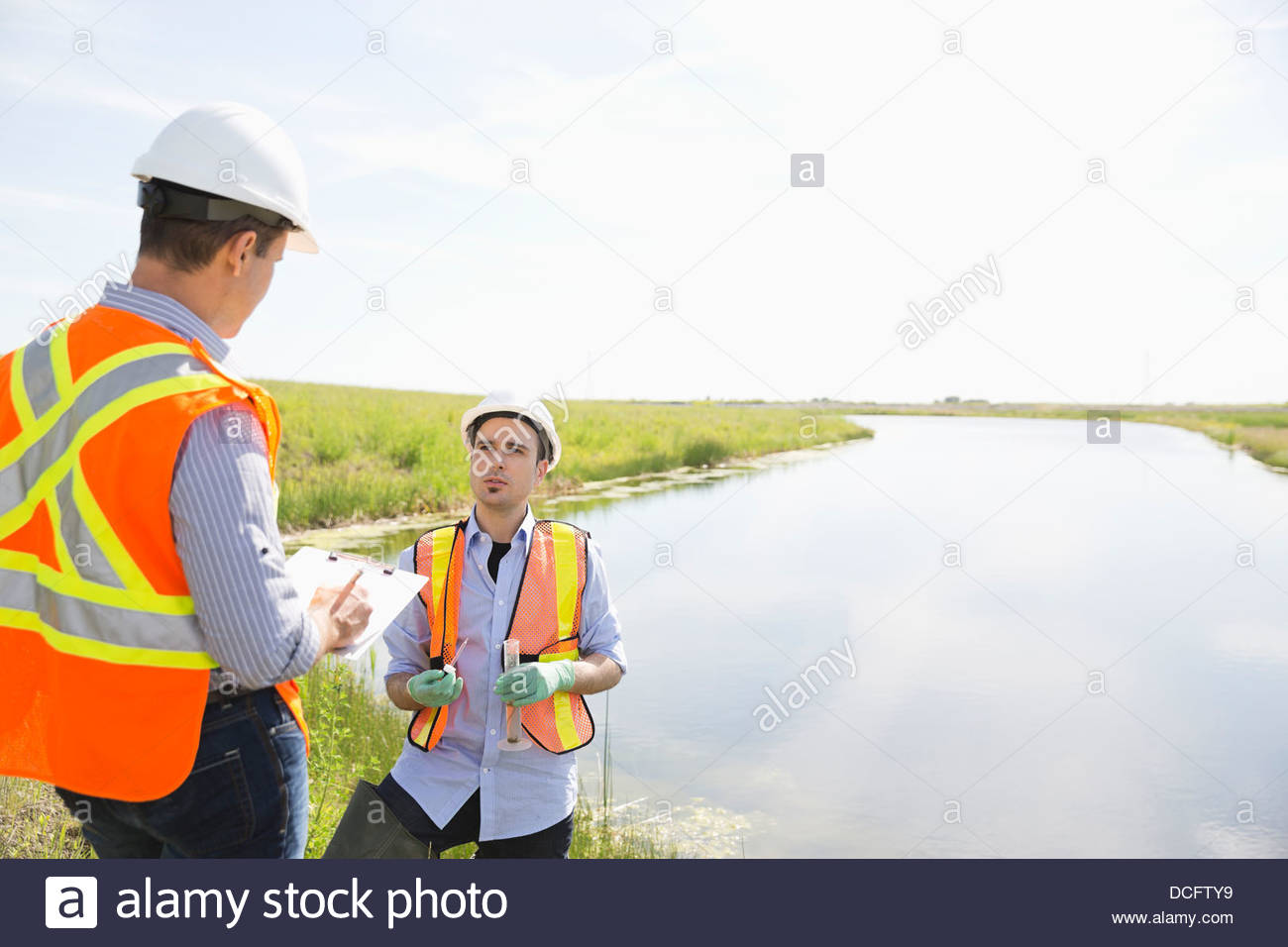 Male ecologists working near a riverbank - Stock Image