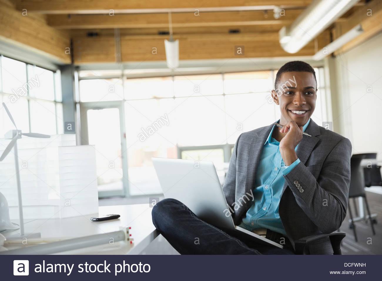 Sustainable energy engineer holding laptop - Stock Image