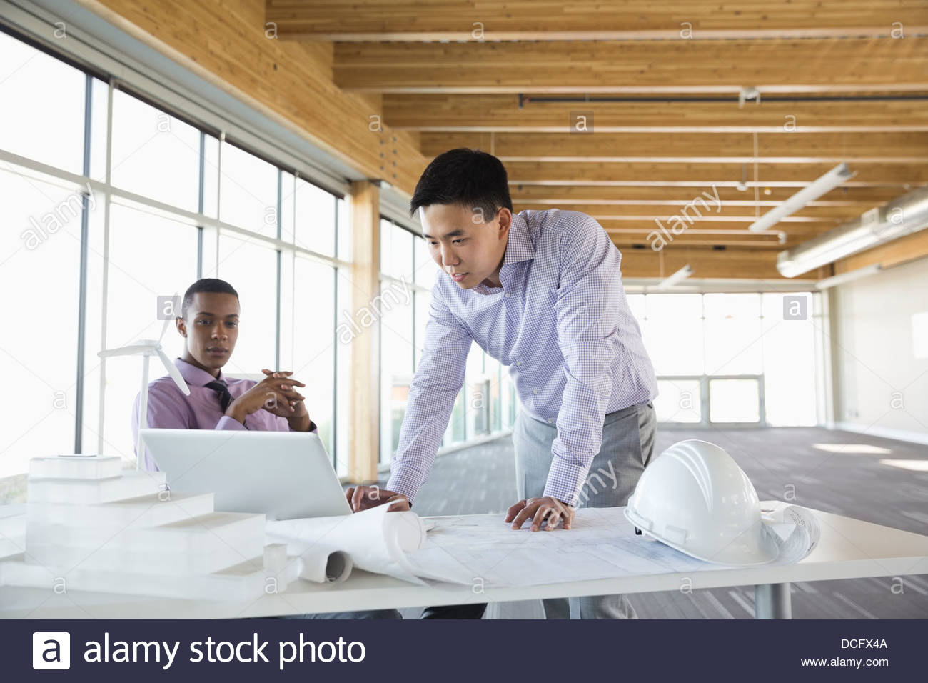 Engineers discussing plans over laptop - Stock Image