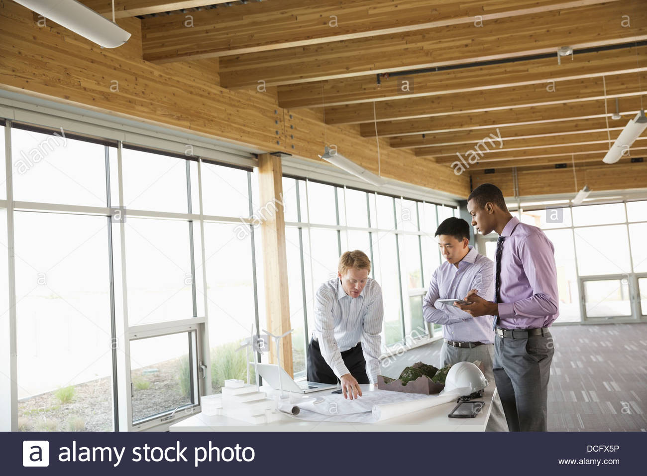 Engineer explaining blueprints to colleagues - Stock Image