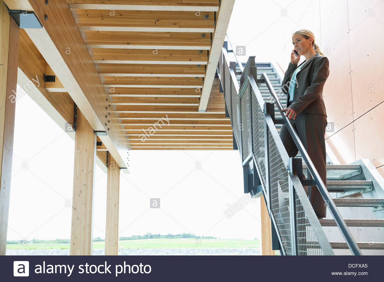 Businesswoman Using Mobile Phone On Staircase   Stock Image