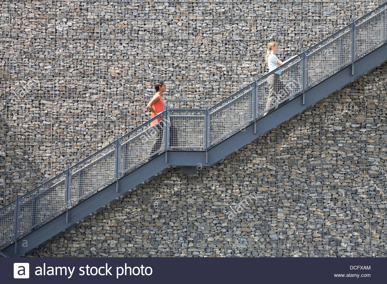 Side view of businesswomen climbing staircase - Stock Image