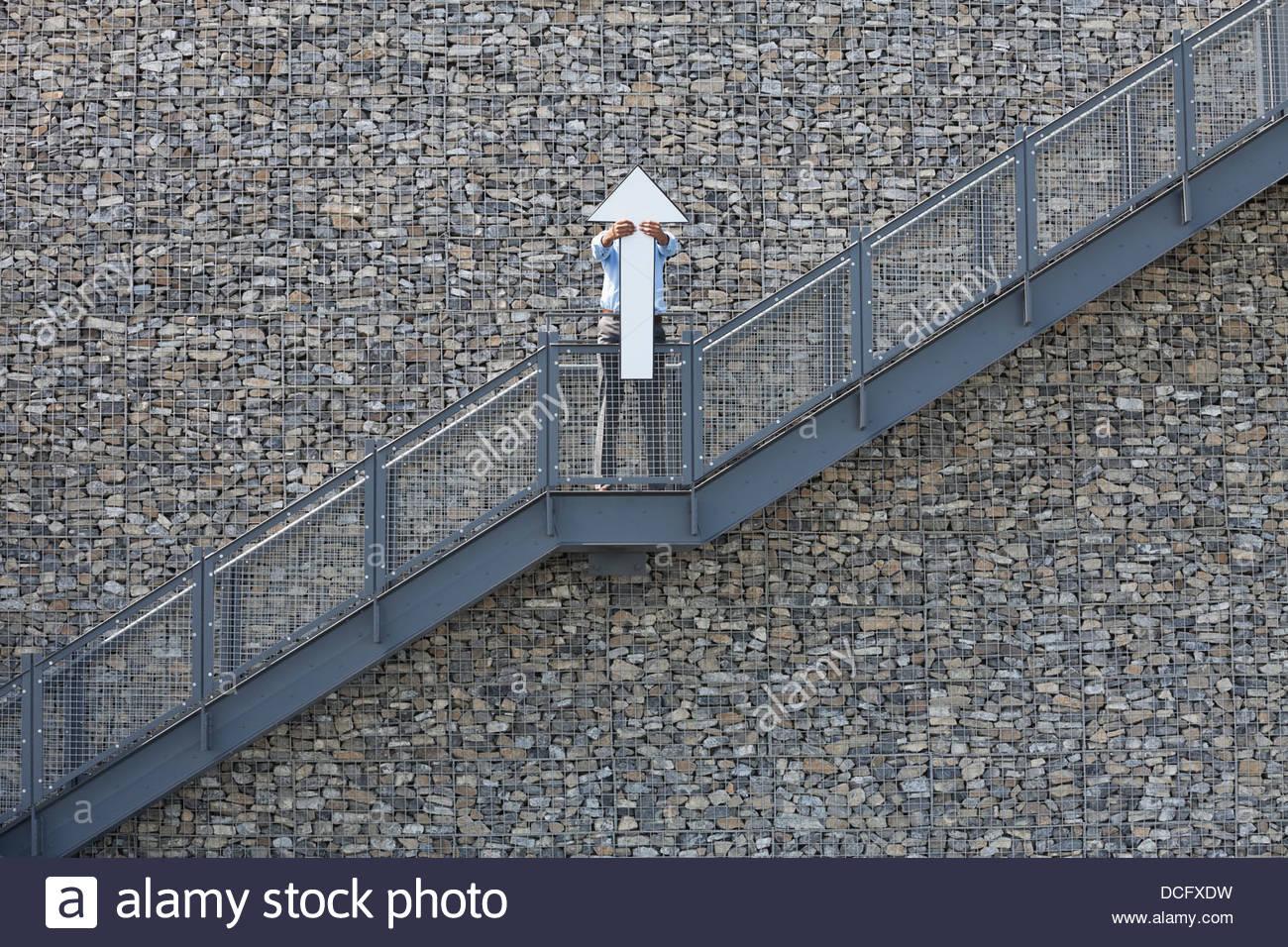 Businessman holding upward arrow - Stock Image