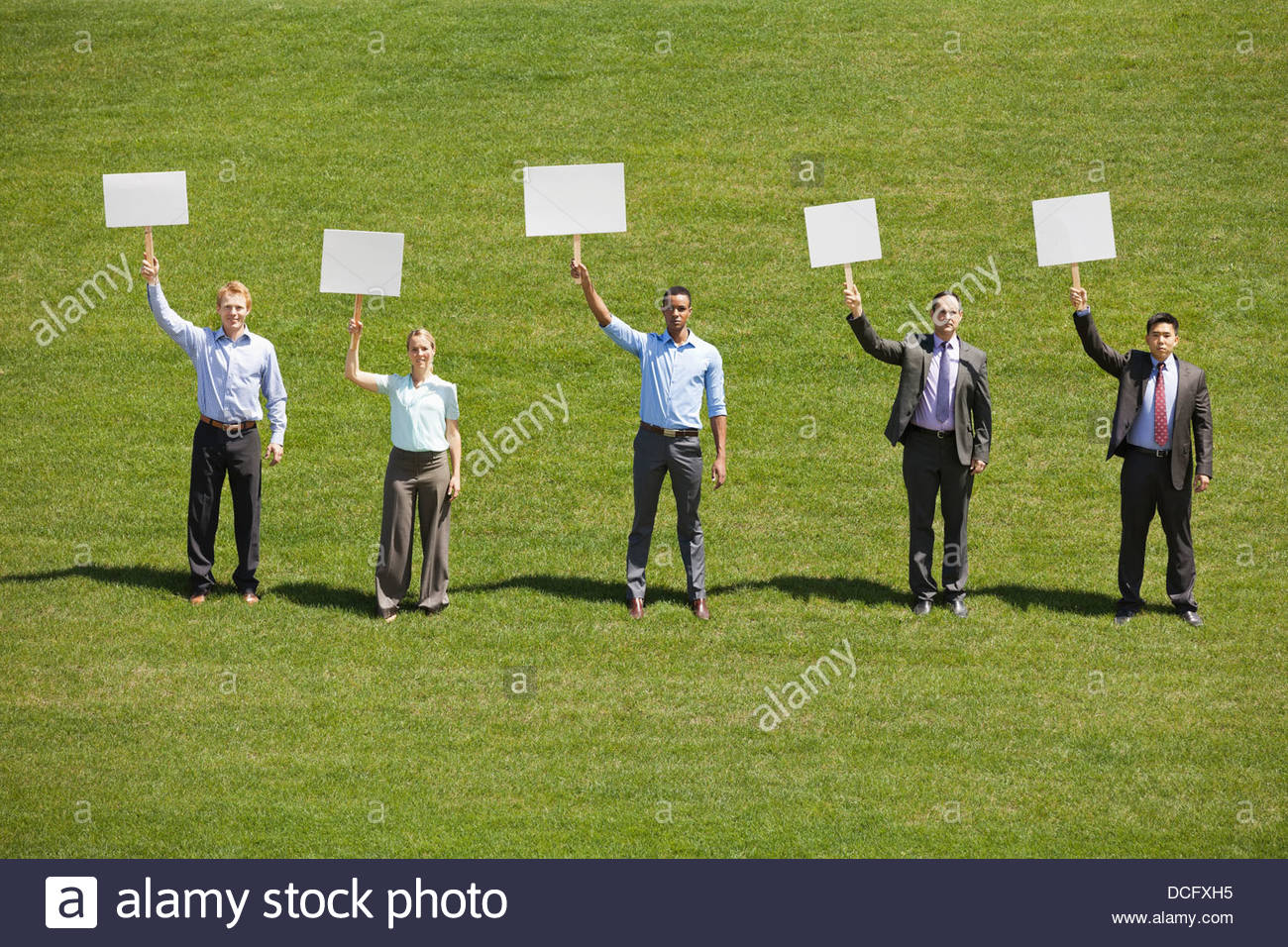 Group of business people holding blank signboards outdoors - Stock Image