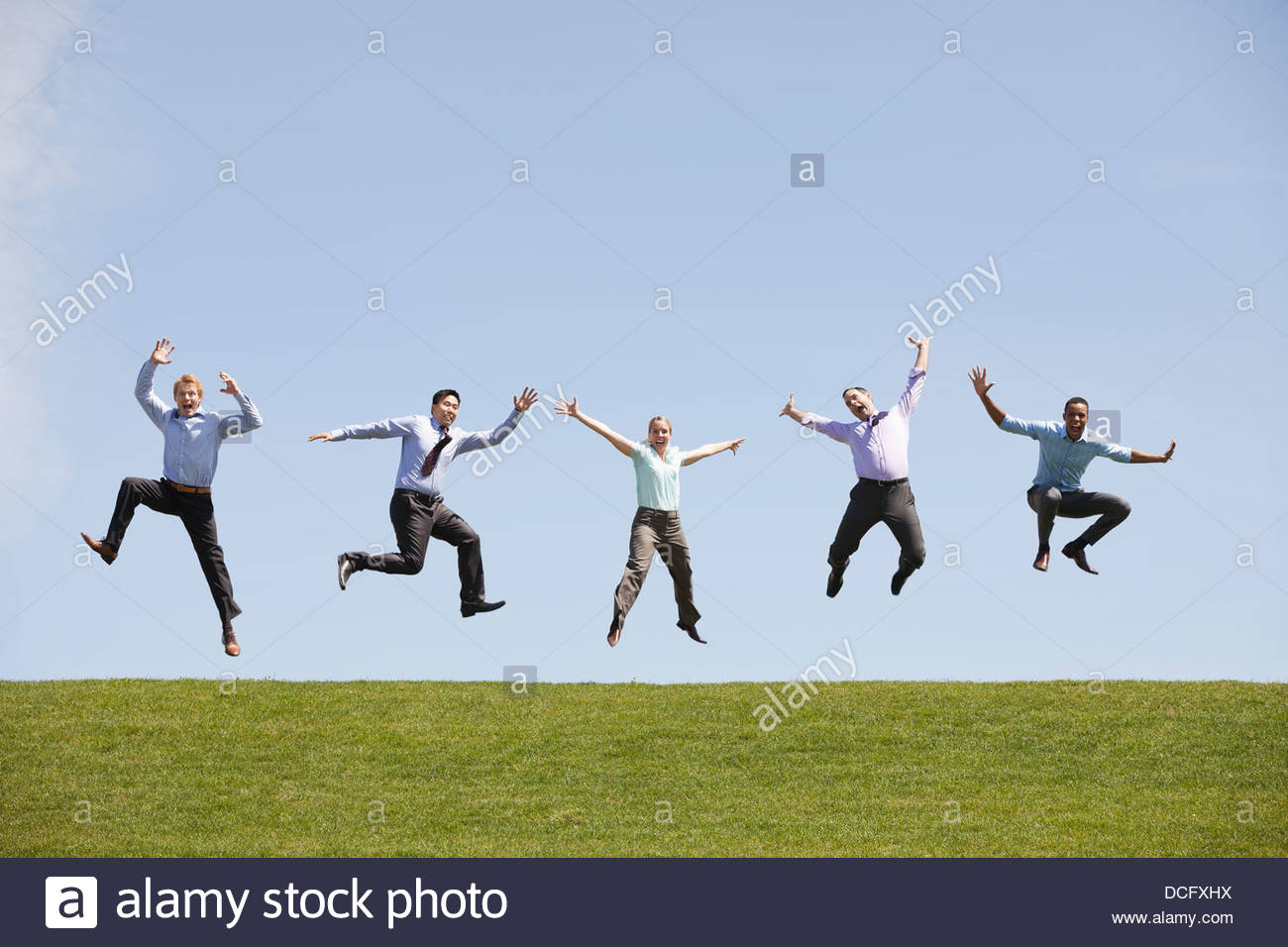 Group of business people jumping simultaneously - Stock Image