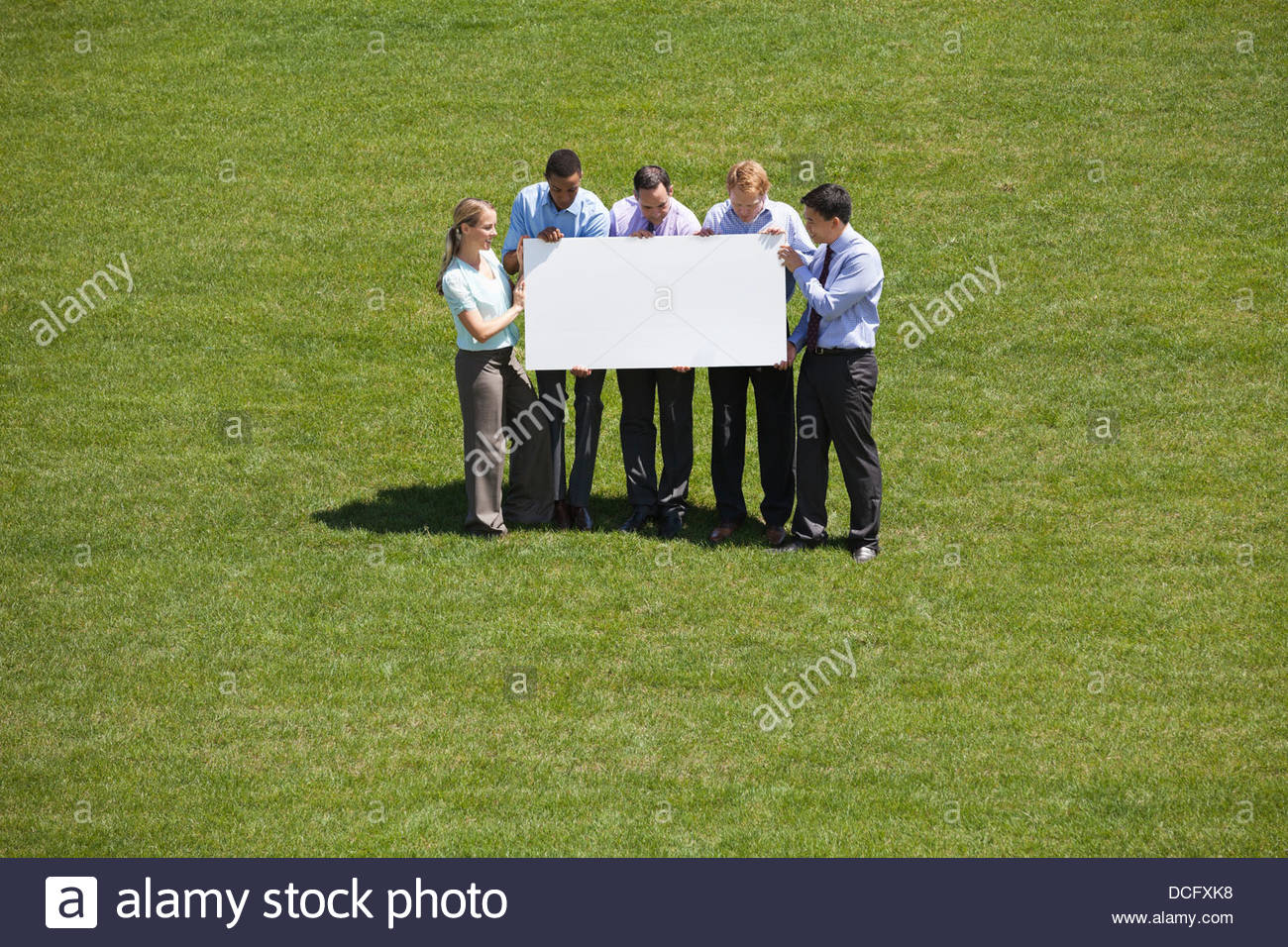 Group of business people displaying blank sign together - Stock Image