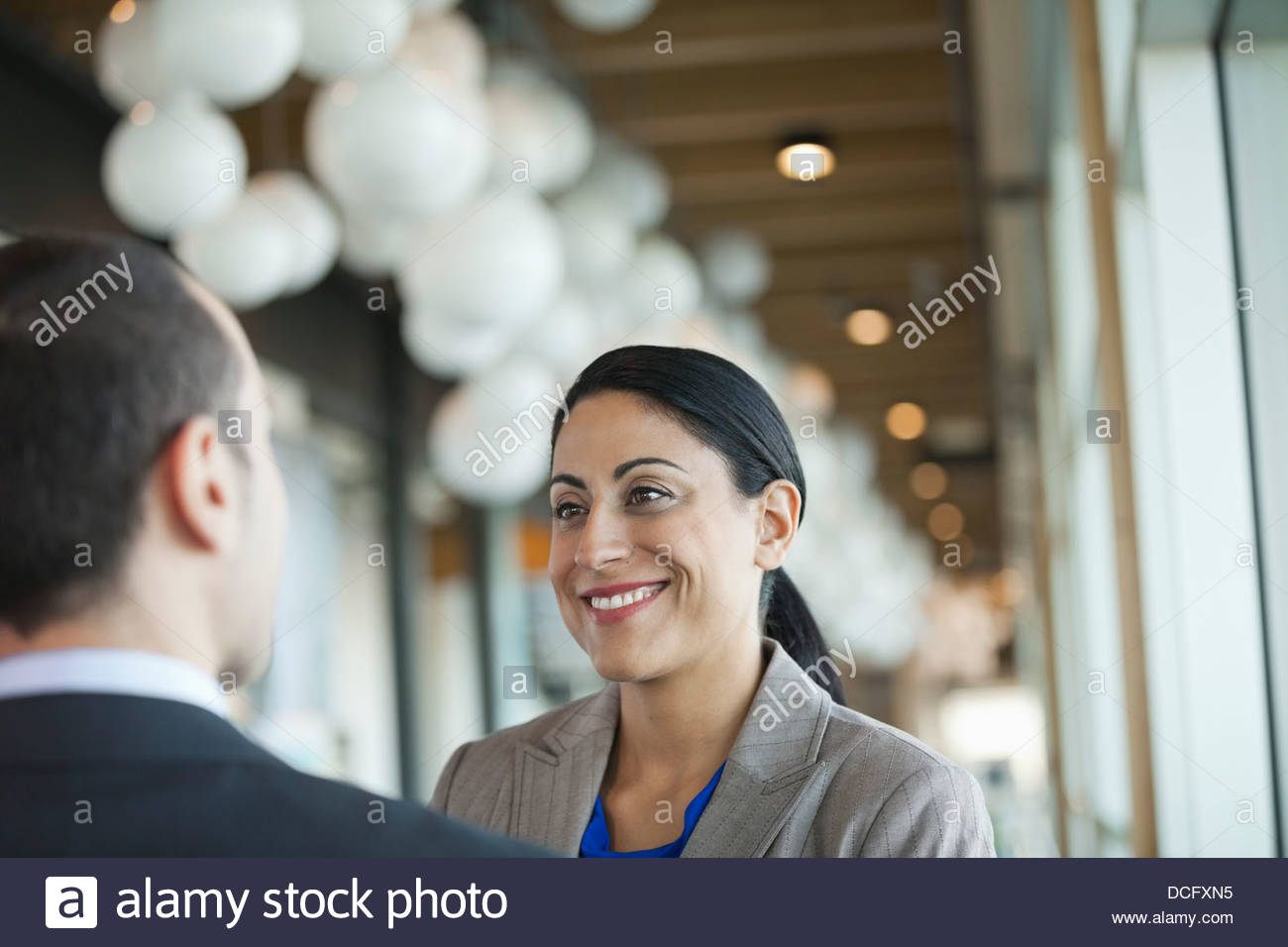 Smiling businesswoman looking at male colleague - Stock Image