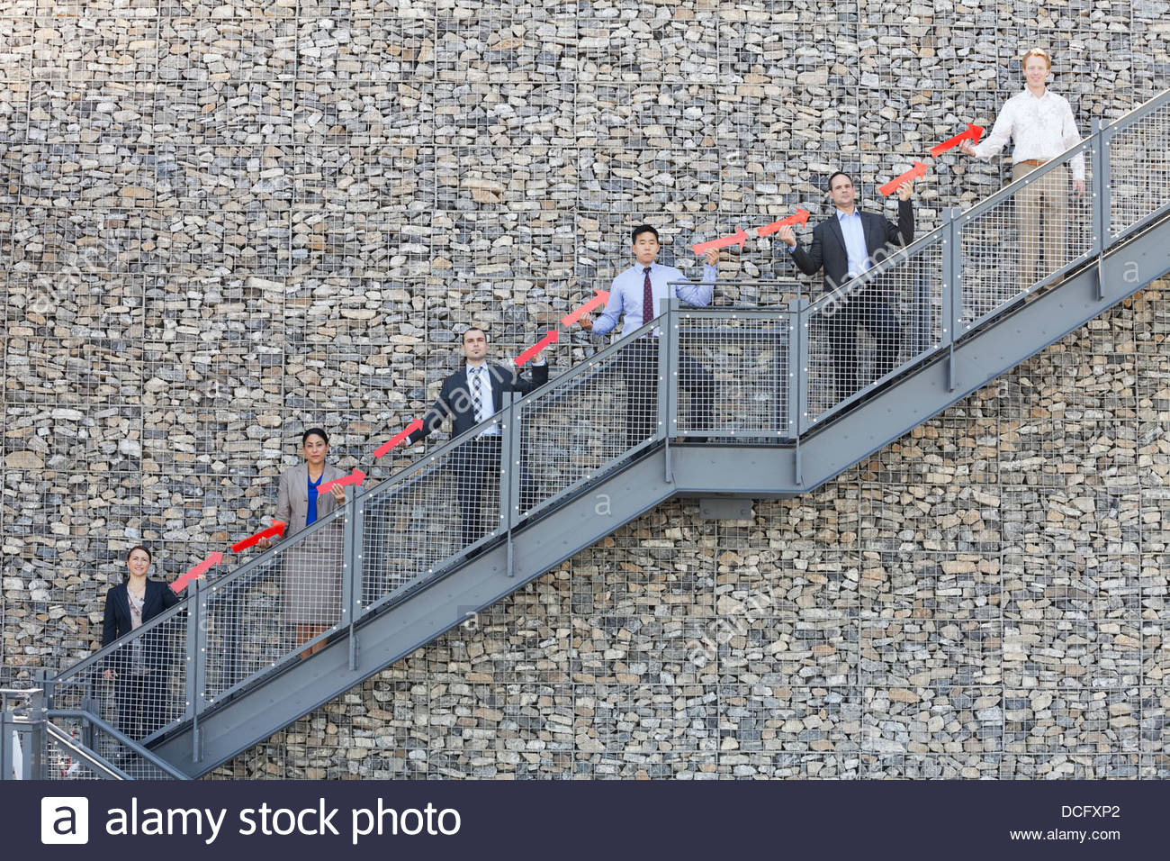 Business people forming upward arrow on staircase - Stock Image