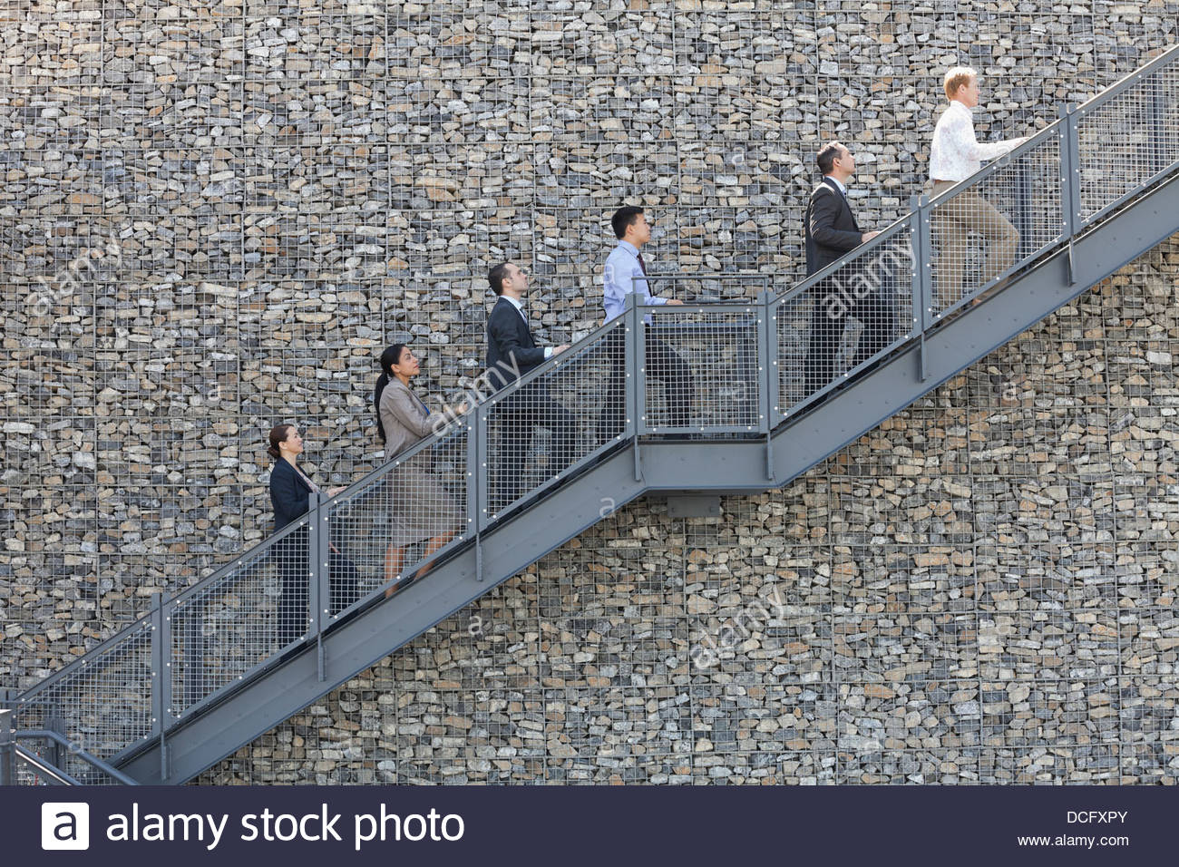 Side view of business people climbing staircase in a line - Stock Image