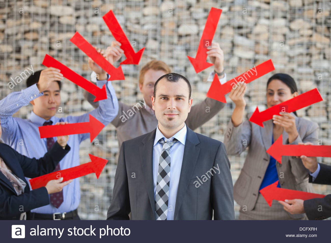 Group of business people pointing arrows towards businessman - Stock Image