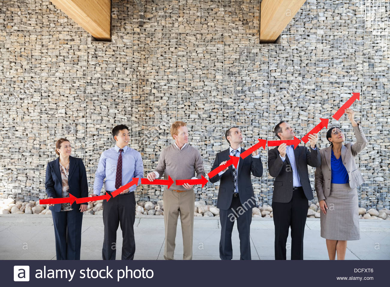 Business people forming upward arrow - Stock Image