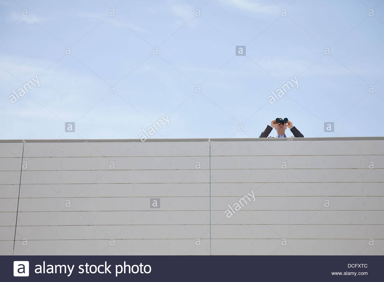 Businessman looking through binoculars on rooftop Stock Photo