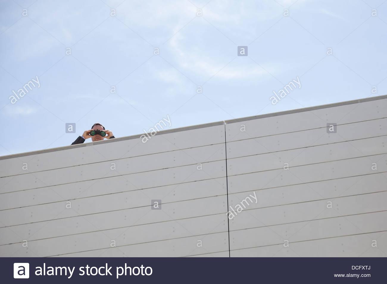 Businessman looking down through binoculars on rooftop - Stock Image