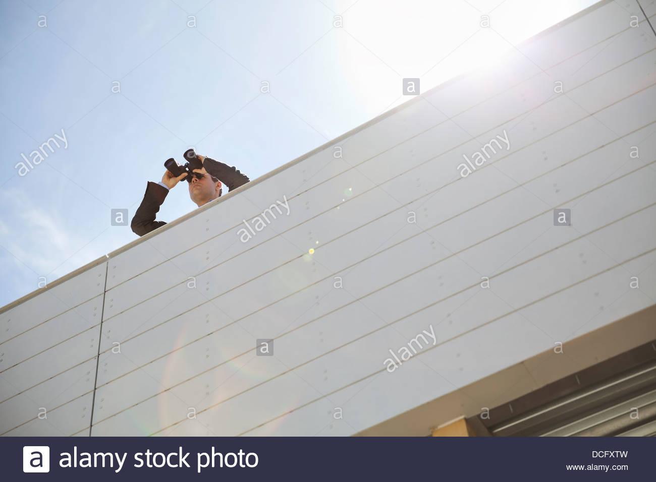 Businessman looking through binoculars on rooftop - Stock Image