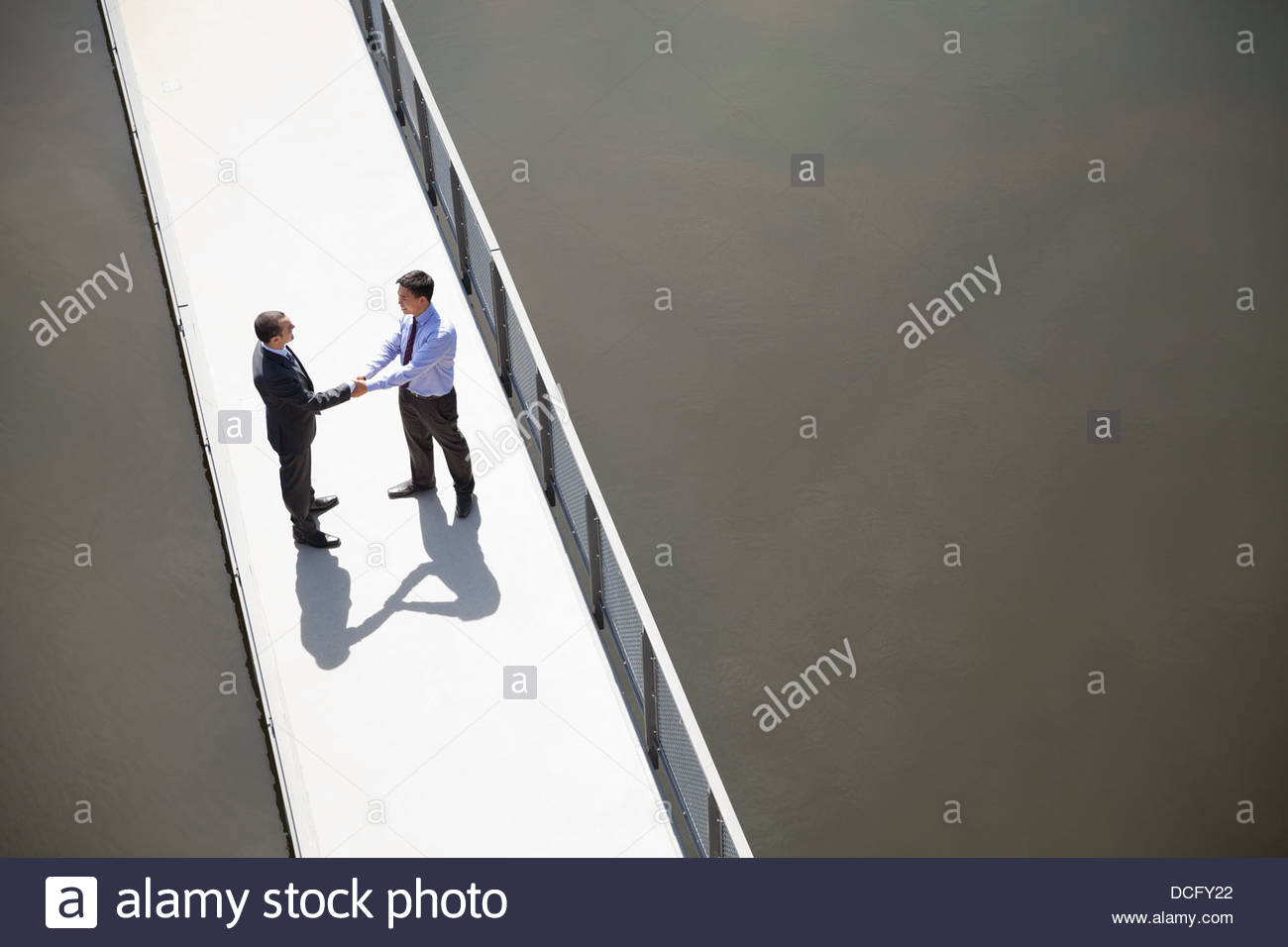High angle view of businessmen shaking hands on bridge - Stock Image