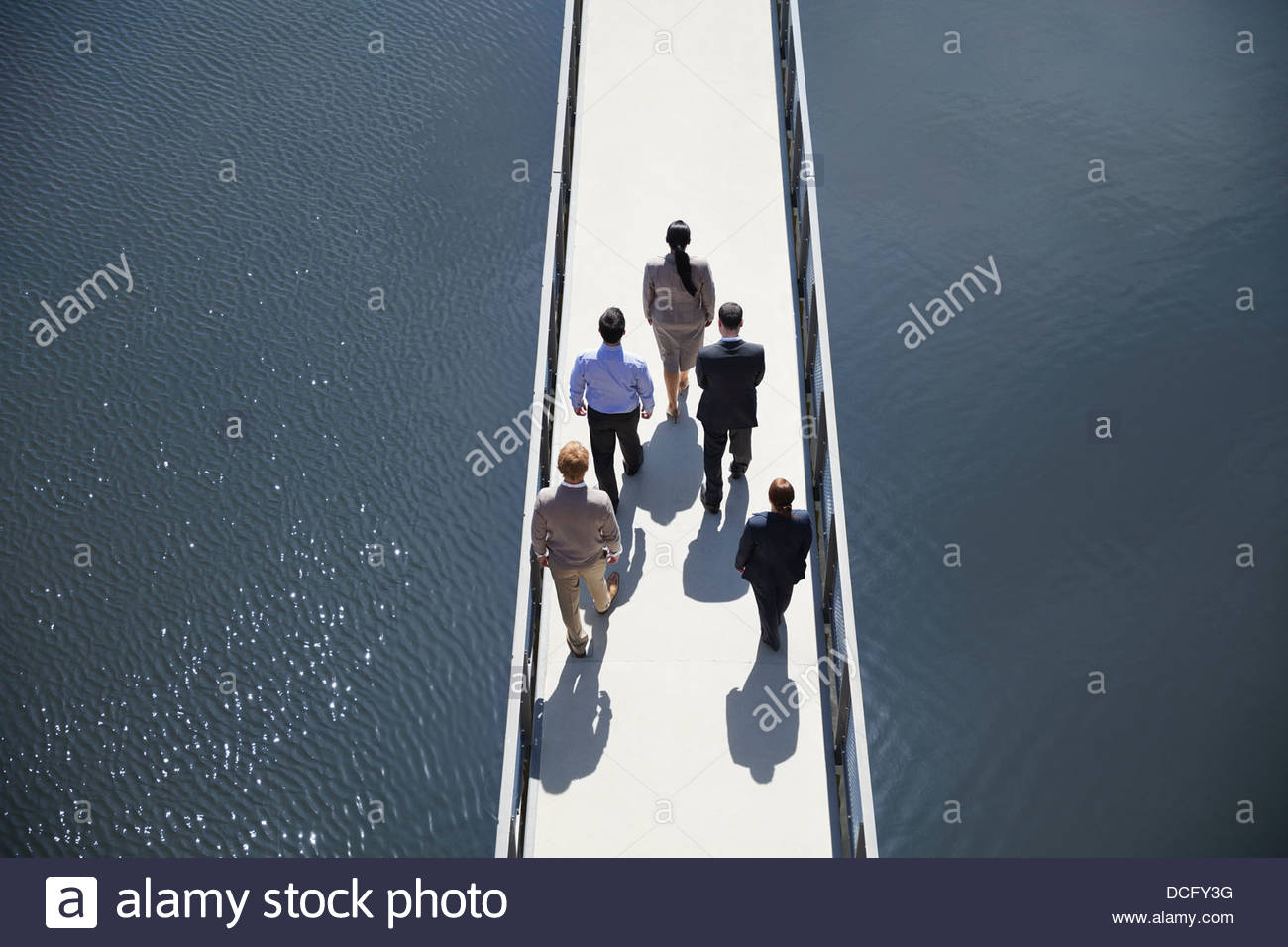 Business people standing in formation on bridge - Stock Image