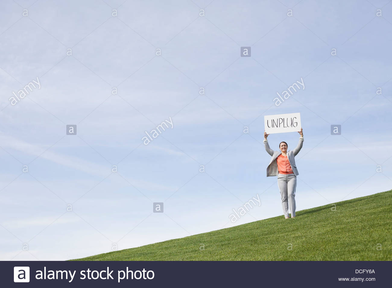 Portrait of businesswoman displaying unplug signboard outside - Stock Image
