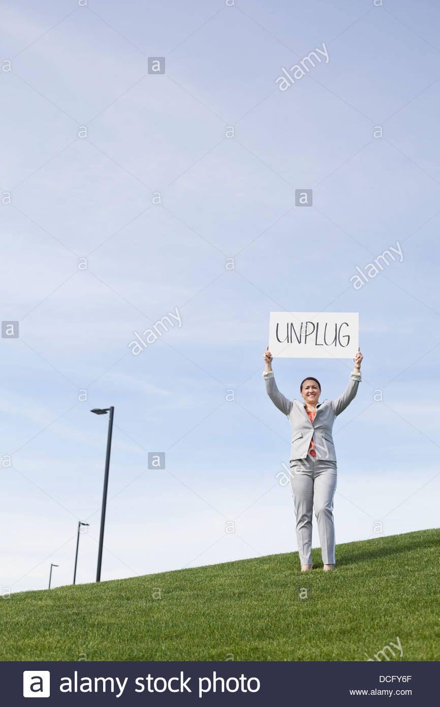 Portrait of businesswoman holding unplug signboard outside - Stock Image