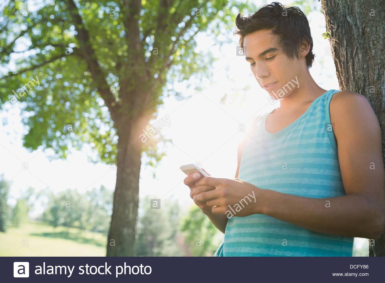 Teenager using smart phone - Stock Image