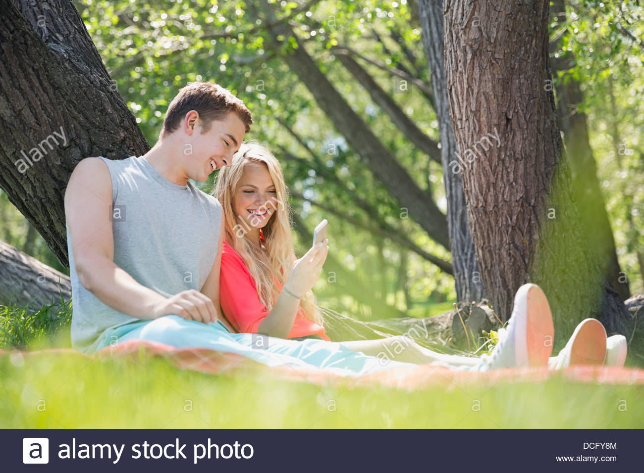 Teens using mobile phone outdoors Stock Photo