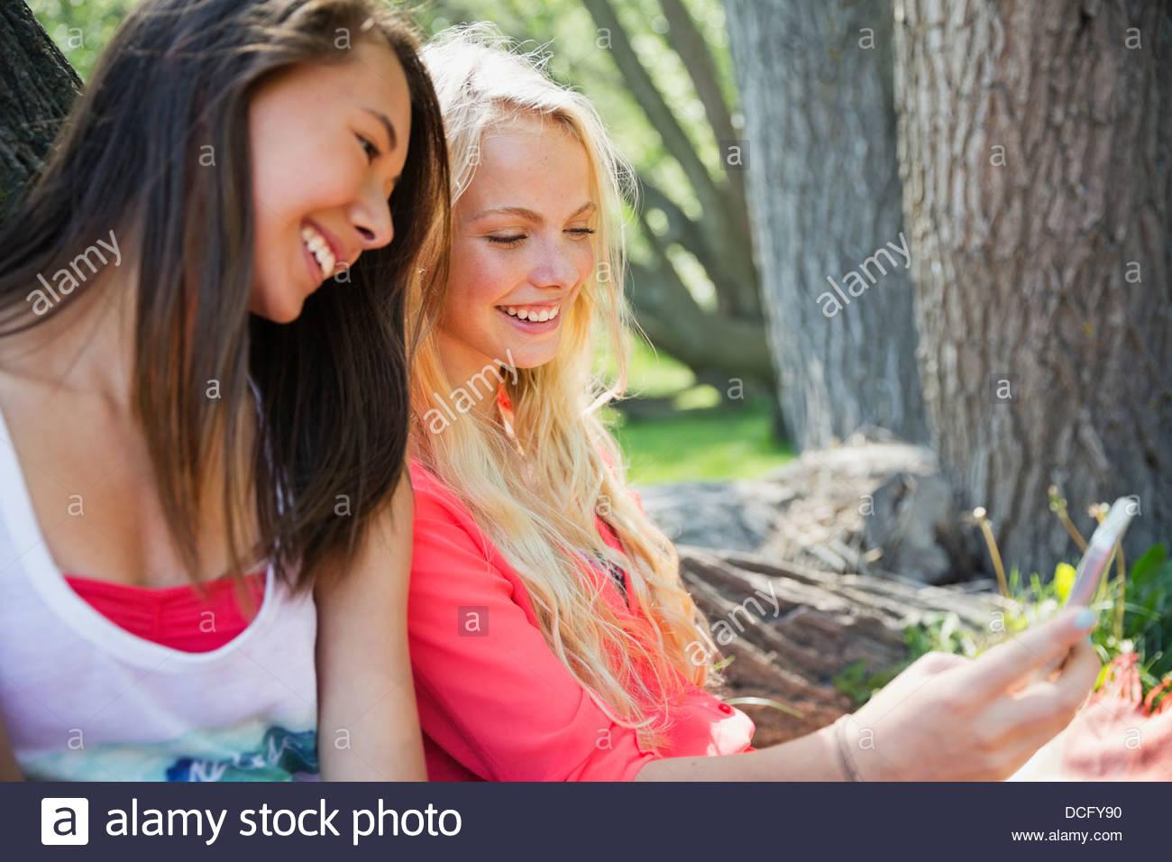 Teenage girls taking self-portrait at park - Stock Image