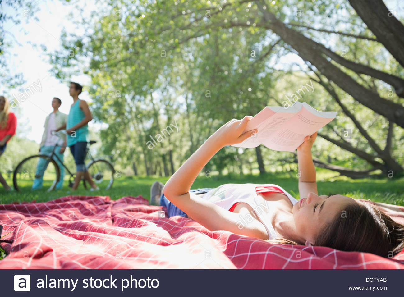 Teenage girl reading book in park - Stock Image