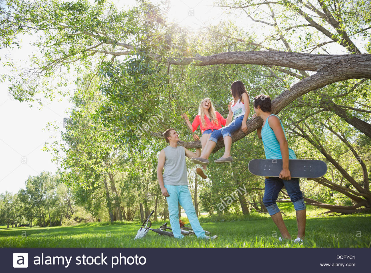 Teenage friends spending time in a park - Stock Image