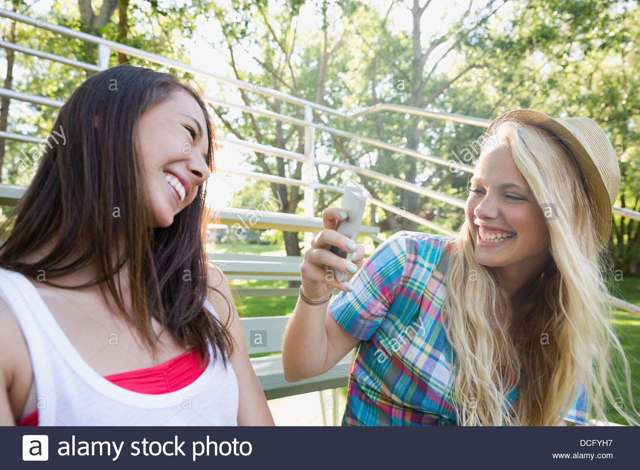 Teenage girl taking picture of friend on smart phone - Stock Image